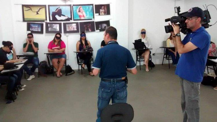 Teco Barbero palestrando em seu workshop. Descrição da Imagem: Teco Barbero no centro da sala falando para os participantes, que estão vendados, enquanto o cinegrafista de uma rede de tv registra tudo para uma matéria no jornal local.