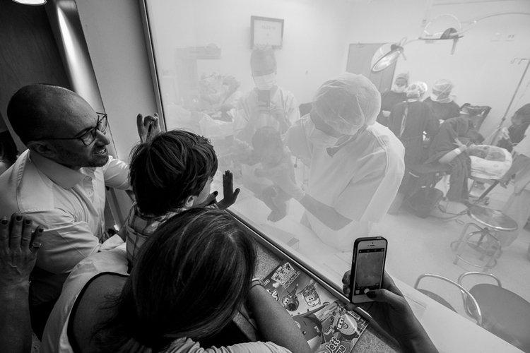 Fotografia: Grazi Ventura. Descrição da imagem: A família, incluindo o irmão mais novo, estão na janela da sala de cirurgia olhando e conhecendo o mais novo membro da família (o bebê) nas mãos do médico.